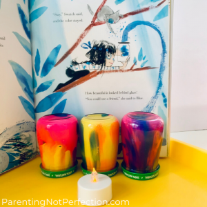 "three marble painted candle holders in front of ""Swatch"" book opened to page showing Swatch capturing blue in a jar."