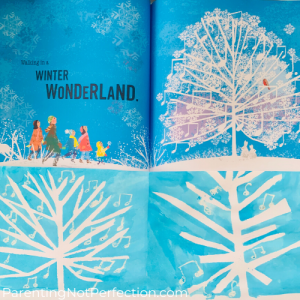 """Walking in a Winter Wonderland"" book open to page showing beautiful musical snowy tree that inspired our tape resist art shown under it"