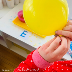 blowing up a yellow balloon through an empty ball point pen to create literacy fun bubble art