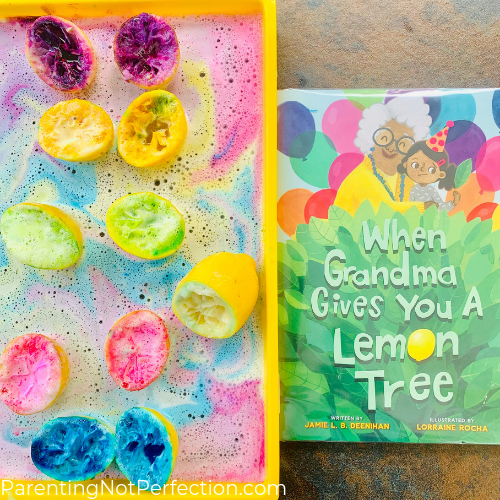"""When Grandma Gives You a Lemon Tree"" book next to lemon volcanoes sitting in a sudsy rainbow"