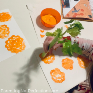 making celery print marigolds with celery and orange paint on white paper