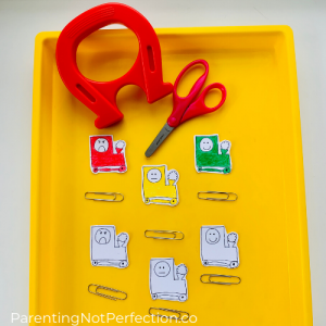 magnet, scissors, paper clips and paper trains both colored & uncolored cut out on yellow tray.