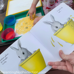 "inside ""White Rabbits Color Book"" showing white bunny in yellow bowl in forefront and hands painting Bunny drawing in background."