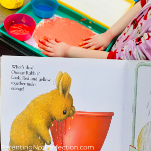 "orange bunny next to red bowl illustration from ""white rabbits color book"" with hands painting bunny drawing orange"