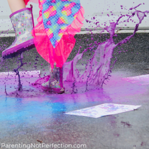 Close up of girls feet wearing rain boots creating puddle painting art