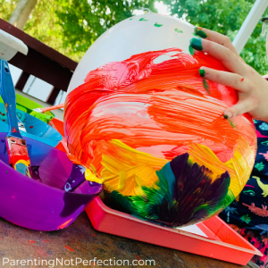 pressing a rainbow painted balloon onto white paper in a red tray