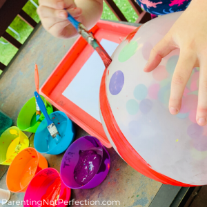 Painting red paint on a confetti filled balloon with a paintbrush