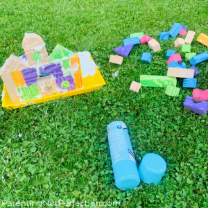 Building blocks and shaving cream castle on a tray in the grass with extra blocks next to it.