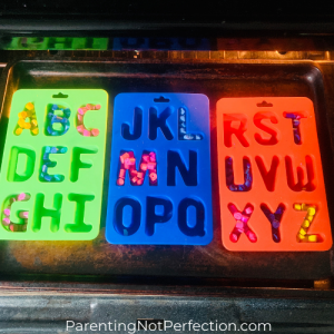 alphabet silicone molds on a cookie tray ready to go into the oven to become recycled crayon letters