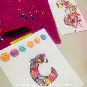 "unwrapped crayons, masterpiece alphabet letter ""C"" printables and crayon wrapper confetti art on a table."