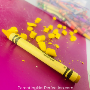 close up of yellow crayon with yellow crayon bits next to it ready to become recycled crayon letters