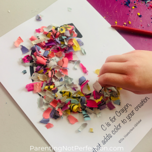 "hand creating crayon wrapper confetti art on a letter ""C"""